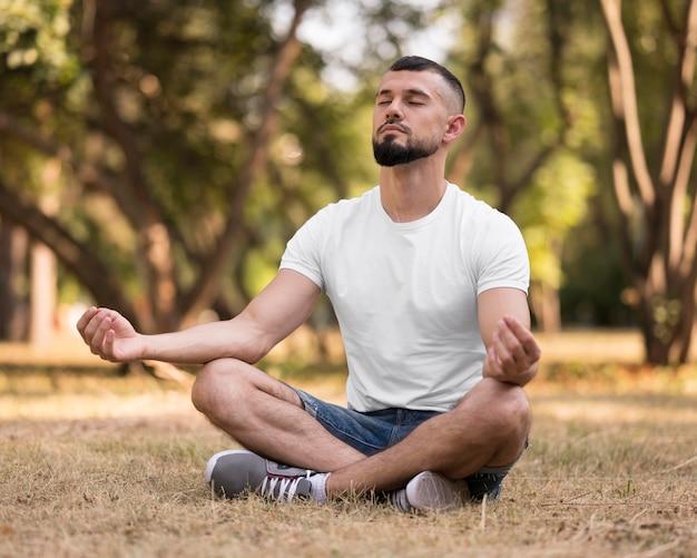 Mężczyzna medytuje na trawie