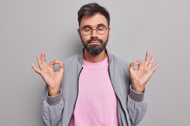 Mężczyzna medytuje sam robi dobry gest obiema rękami oddycha głęboko z zamkniętymi oczami ćwiczy joga nosi okrągłe okulary szara kurtka różowa koszulka