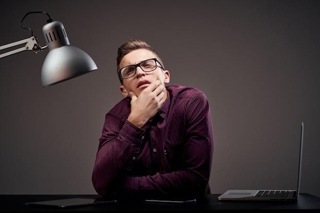 Mężczyzna menedżer w biurze zdziwiony wygląd szafki lampy w miejscu pracy.