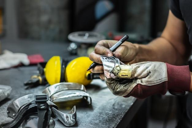 Mężczyzna metalowiec konstruujący i składający kawałek średniowiecznej zbroi. ręce człowieka do pracy z metalowymi częściami sprzętu w warsztacie