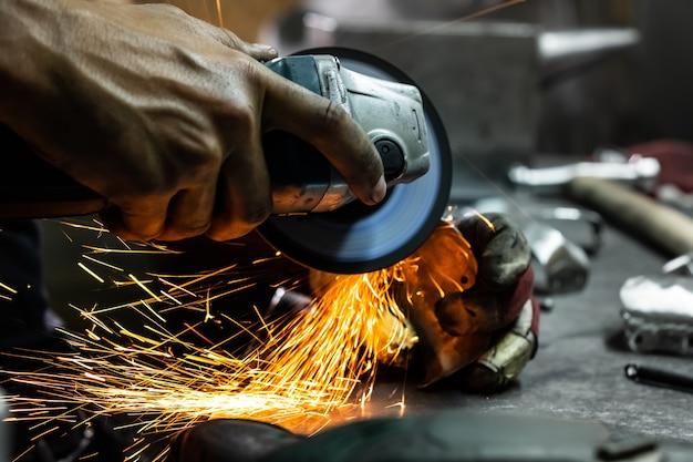 Mężczyzna metalowiec polerujący i wykańczający kawałek średniowiecznej zbroi. ręce człowieka obróbki metalowych części sprzętu w warsztacie szlifierką kątową.