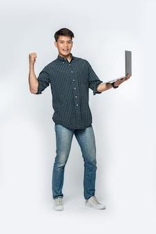 Mężczyzna miał na sobie białą koszulę i ciemne spodnie, trzymał laptopa i udawał radosnego