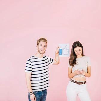 Mężczyzna mienia aprobat znak obok uśmiechniętego kobiety mienia smartphone
