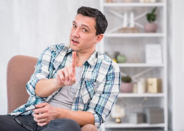 Mężczyzna mienia eyeglasses i pokazywać palec wskazującego na krześle w domu