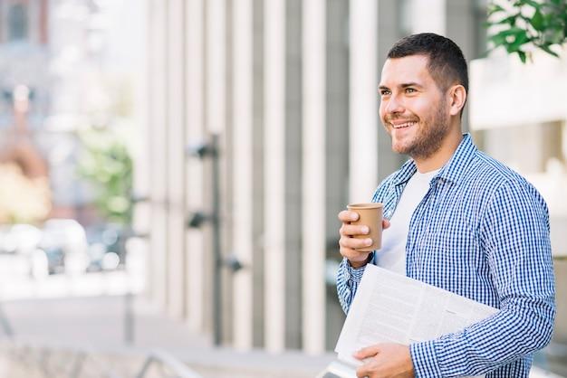 Mężczyzna mienia gazeta i kawowy pobliski budynek