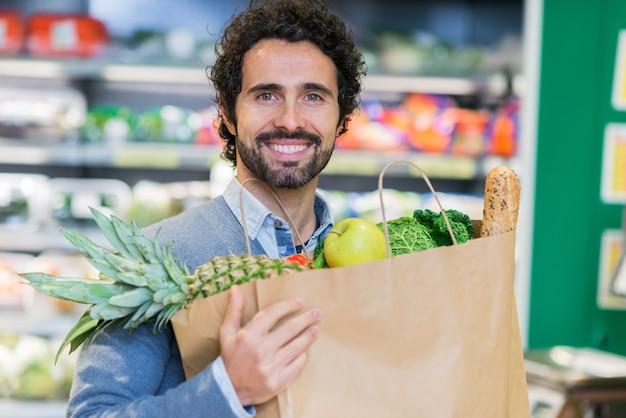 Mężczyzna mienia karmowa torba w sklepie spożywczym