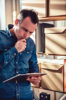 Mężczyzna mienia klamerki deska i czytanie dokument przy biurem