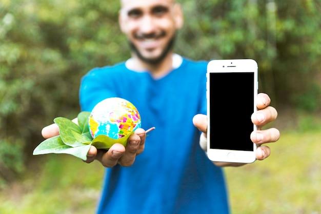 Mężczyzna mienia kula ziemska z liściem i smartphone