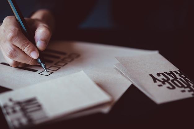 Mężczyzna mienia pióro zaznaczać na głosowania papierze
