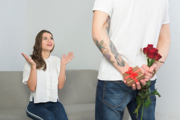 Mężczyzna mienia prezenty dla młodej kobiety za plecy