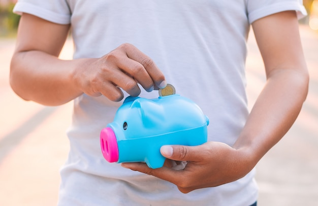 Mężczyzna mienia prosiątka bank, ratuje pieniądze pojęcie.