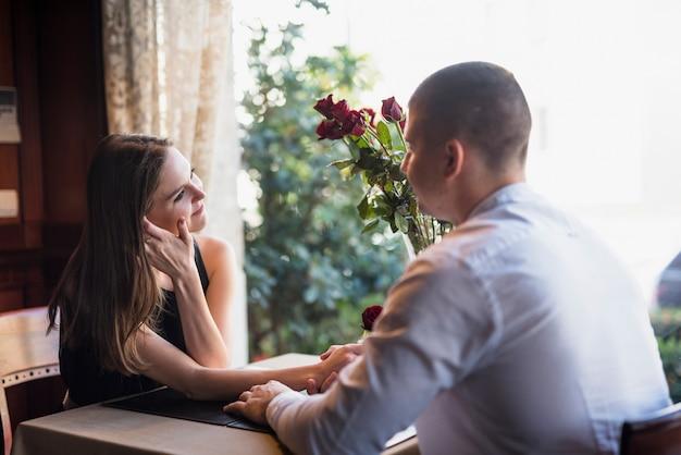 Mężczyzna mienia ręka młoda kobieta i obsiadanie przy stołem