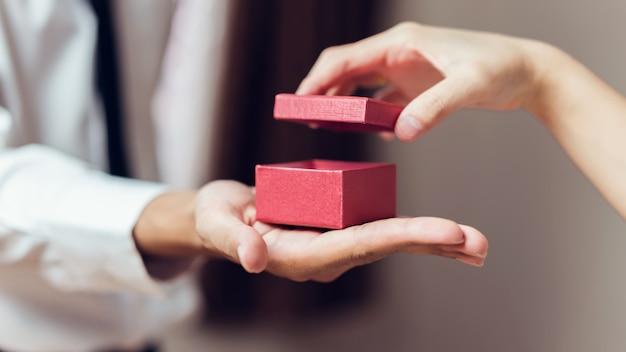 Mężczyzna mienie otwiera pustego czerwonego prezenta pudełko.