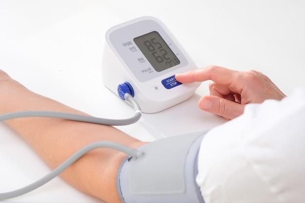 Mężczyzna mierzy ciśnienie krwi, białe tło. niedociśnienie tętnicze. ręka i tonometr z bliska.