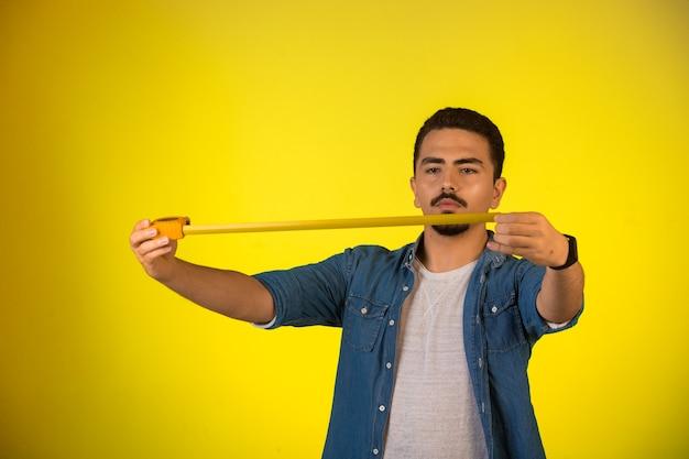 Mężczyzna mierzy długość linijką.