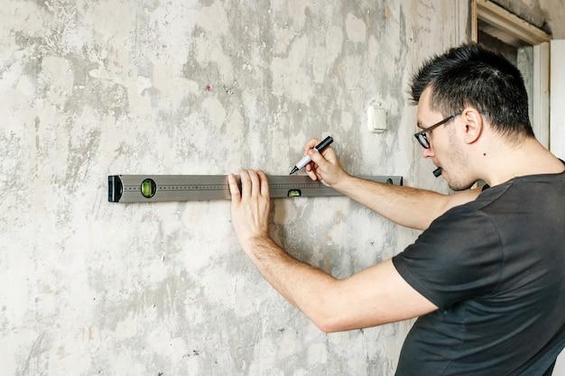 Mężczyzna mierzy na ścianie linijką