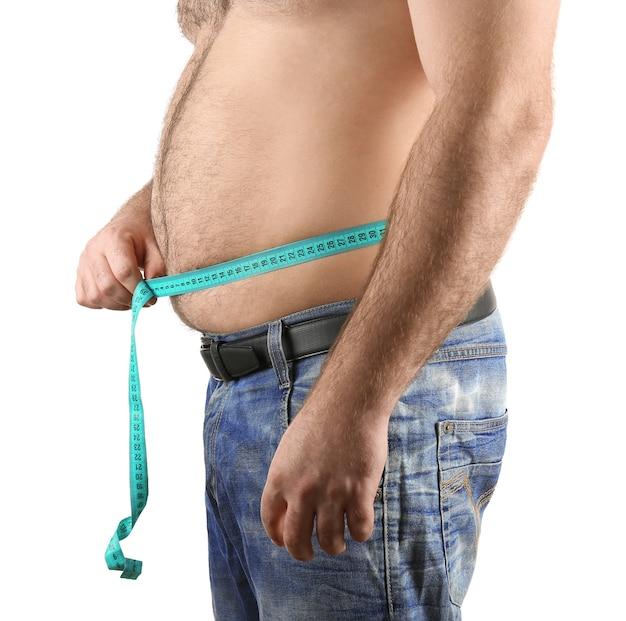 Mężczyzna mierzy piwny brzuch na białym tle