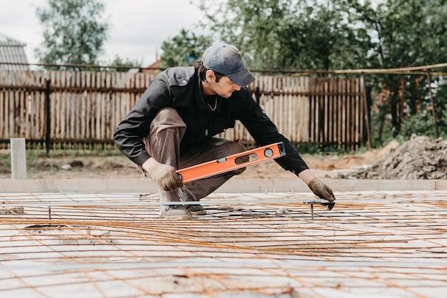 Mężczyzna mierzy poziom konstrukcji prętów zbrojeniowych do posadowienia domu w budowie