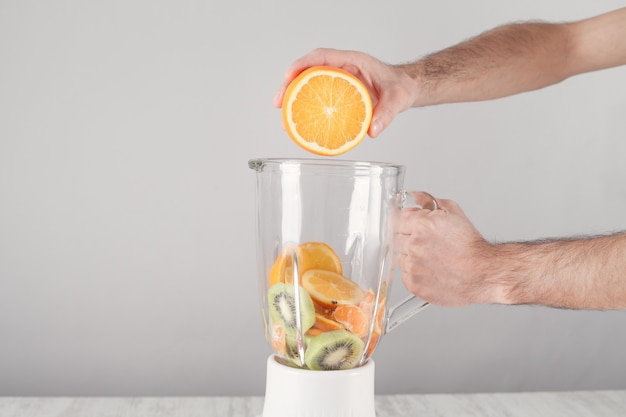 Mężczyzna mieszanie owoców z elektrycznym blenderem.