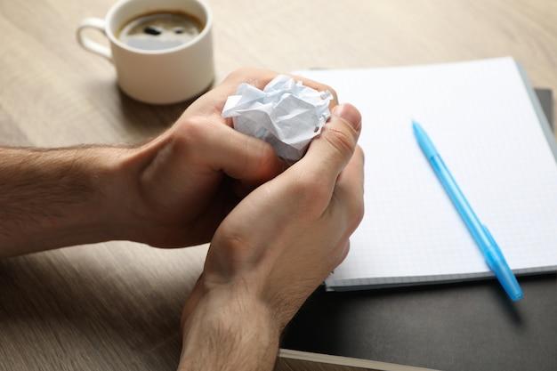 Mężczyzna mięta papier na drewno stole z copybook i filiżanką kawy, zamyka up