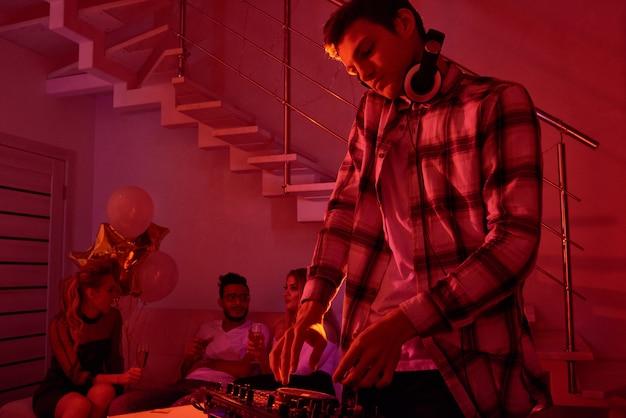 Mężczyzna miksuje muzykę na przyjęciu gwiazdkowym