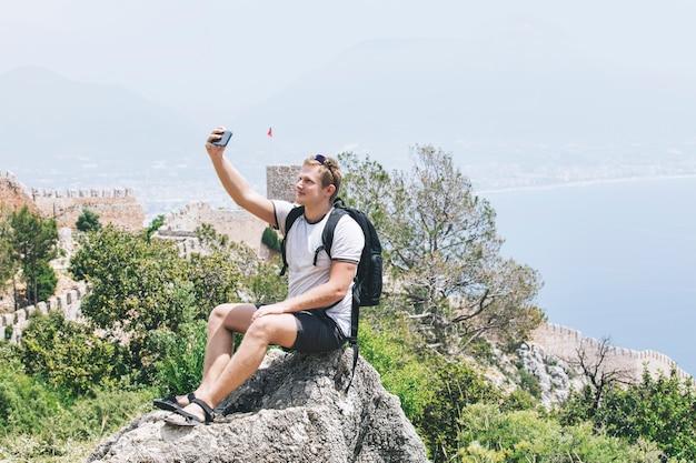 Mężczyzna młody dorosły z telefonem komórkowym w krajobrazie z morzem