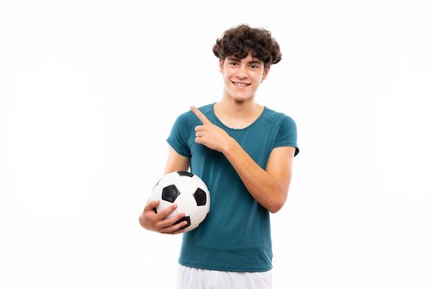 Mężczyzna młody piłkarz na pojedyncze białej ścianie, wskazując na bok, aby przedstawić produkt