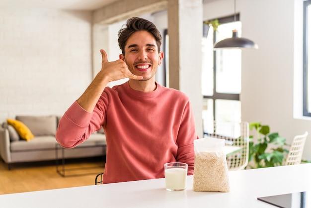 Mężczyzna młody rasy mieszanej jedzenie płatków owsianych i mleka na śniadanie w kuchni pokazując gest połączenia z telefonem komórkowym palcami.