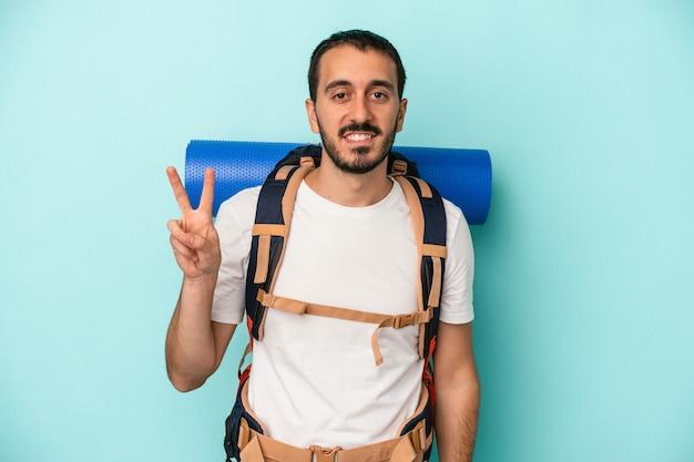 Mężczyzna młody turysta kaukaski na białym tle na niebieskim tle wyświetlono numer dwa palcami.