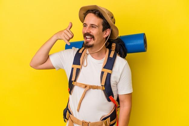 Mężczyzna młody turysta kaukaski na białym tle na żółtym tle pokazano gest połączenia z telefonu komórkowego palcami.