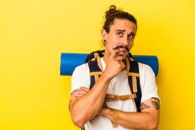 Mężczyzna młody turysta kaukaski z długimi włosami na białym tle na żółtym tle zrelaksowany myśli o czymś patrząc na miejsce.