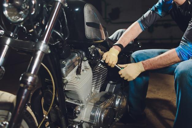 Mężczyzna mocowania roweru. ufny młody człowiek naprawia motocykl blisko jego garażu.