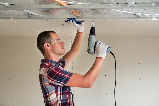 Mężczyzna mocowania sufitu podwieszanego suchej zabudowy do metalowej ramy