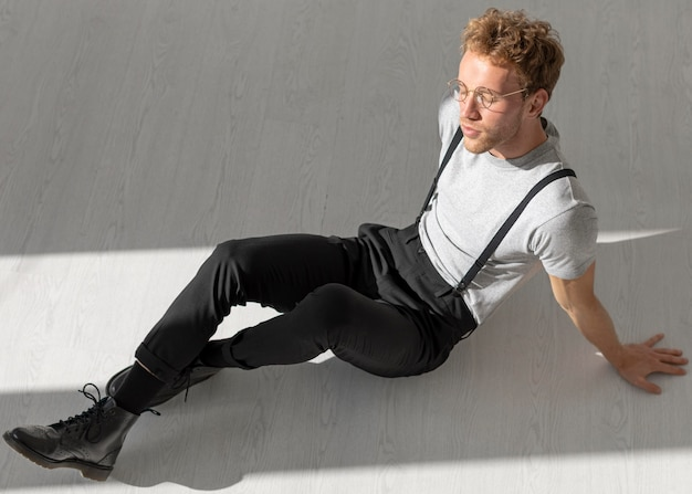 Mężczyzna model siedzi na podłodze z zamkniętymi oczami wysoki widok