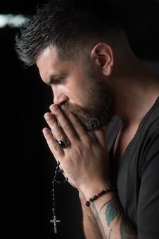 Mężczyzna modlący się za ręce z różańcem w nadziei na najlepsze ludzkie emocje wyraz twarzy czujący modlitwę