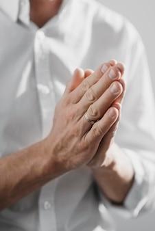 Mężczyzna modli się sam w domu z bliska