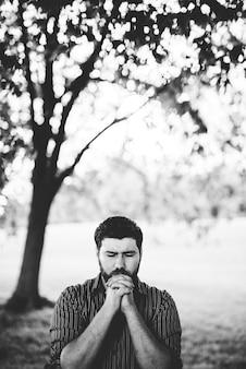 Mężczyzna modli się w parku