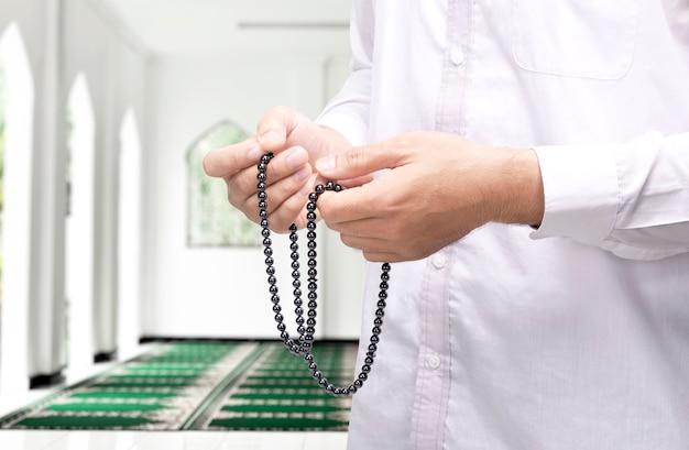 Mężczyzna modli się z paciorkami modlitewnymi na rękach na meczecie