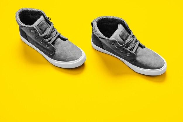 Mężczyzna mody popielaci buty odizolowywający na kolor żółty powierzchni.