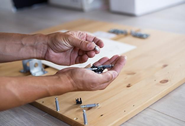 Mężczyzna montaż mebli w domu, męska ręka z drewnianymi kołkami i śrubami.