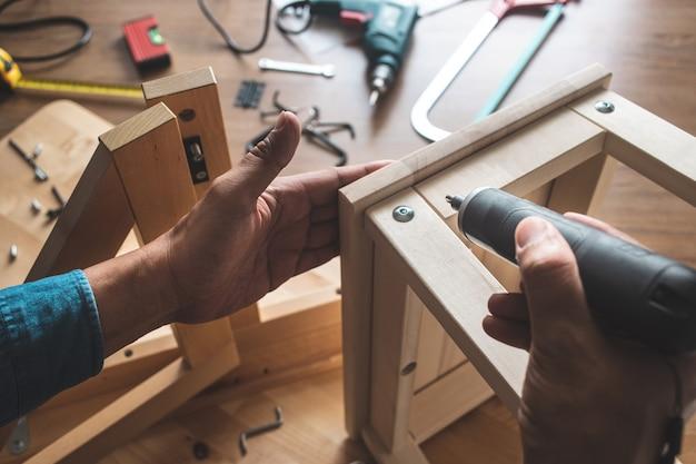 Mężczyzna montuje drewniane meble, naprawiając lub naprawiając dom