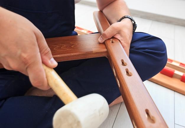 Mężczyzna montuje drewniane meble w domu