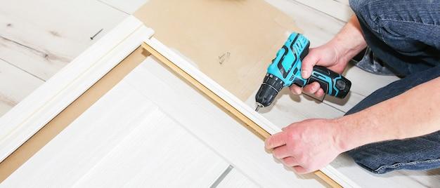 Mężczyzna montuje drzwi. cieśla wykonuje otwory wiertłem w zawiasach. prace naprawcze. konserwacja w mieszkaniu.
