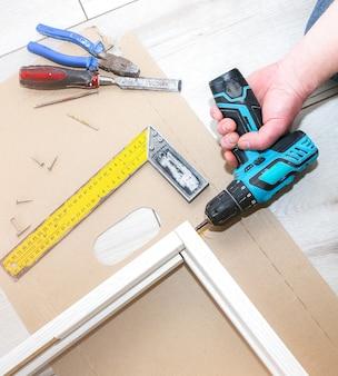 Mężczyzna montuje drzwi. stolarz trzyma wiertło w rękach. prace naprawcze. konserwacja w mieszkaniu.
