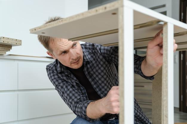 Mężczyzna montuje meble w domu