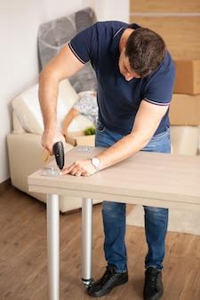 Mężczyzna montuje meble w swoim nowym mieszkaniu. człowiek za pomocą narzędzi.