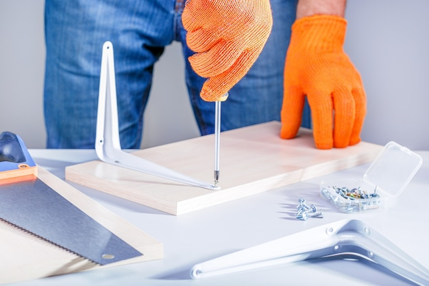 """Mężczyzna montuje meble za pomocą śrubokręta. koncepcja """"zrób to sam""""."""