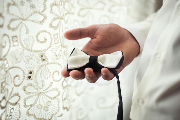 Mężczyzna motyl ubrania, biznesmen stawiając na muszkę. garnitur, ręce, pielęgnacja, krawat, poprawianie, dostosowywanie, moda, kokarda.