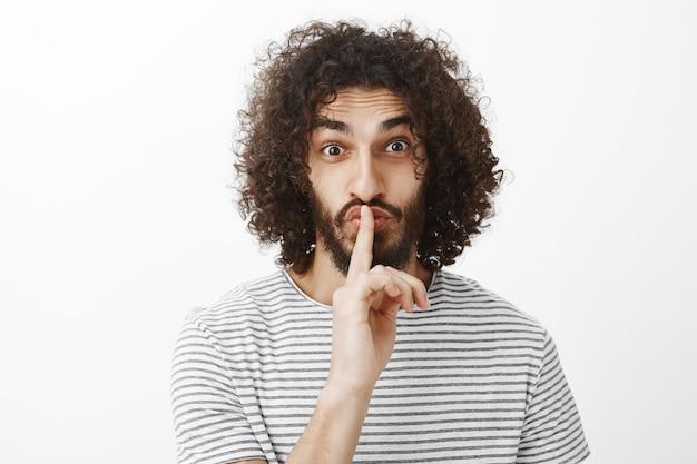 Mężczyzna mówi cii, pokazując gest ciszy z palcem wskazującym na ustach