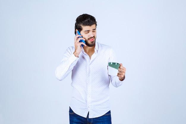Mężczyzna mówi do swojego niebieskiego smartfona nowego modelu
